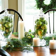 fruit and tall vases with candles and greenery Christmas table