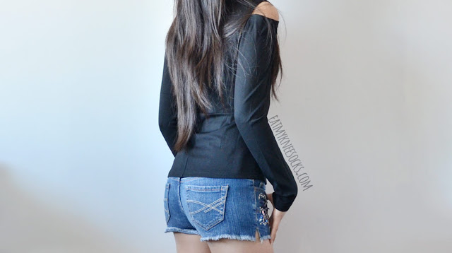 A casual, simple outfit featuring SheIn's black long-sleeve cold shoulder choker-style cutout T-shirt and embellished denim shorts.