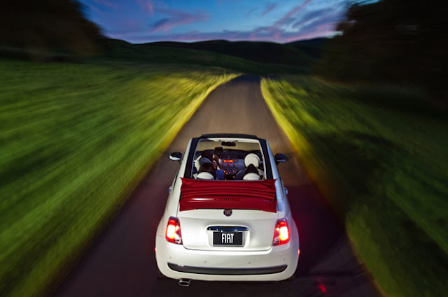 Rear view from above of 2012 Fiat 500C driving on a narrow road at dusk with the roof retracted