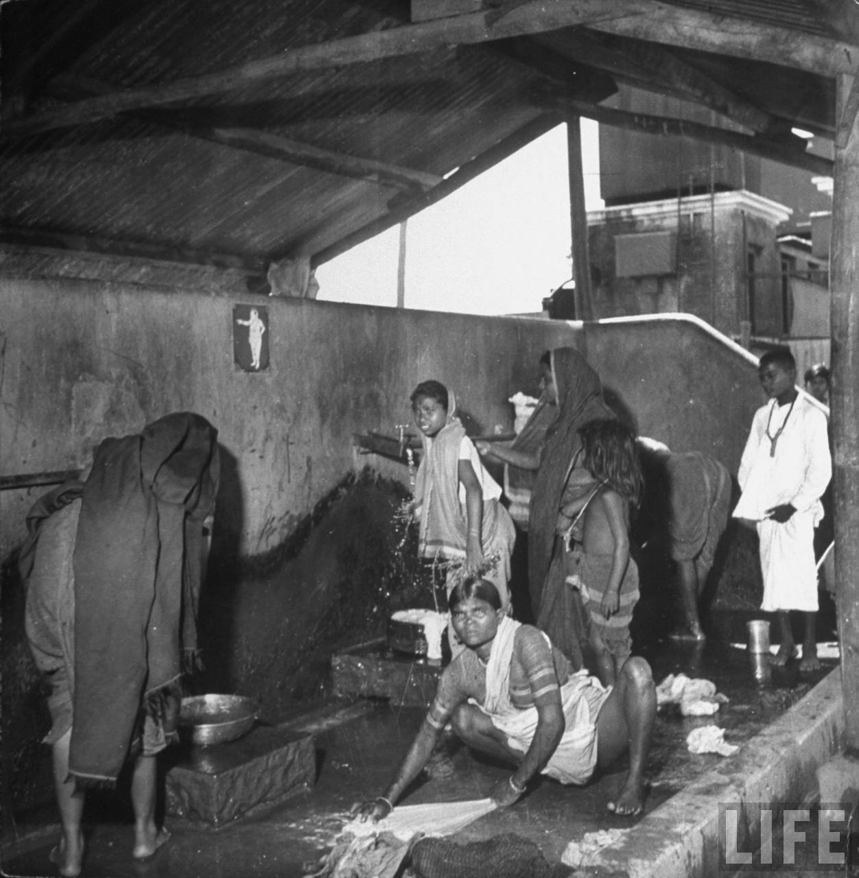 Indian women washing clothes at the public water stands in the Chawls ...