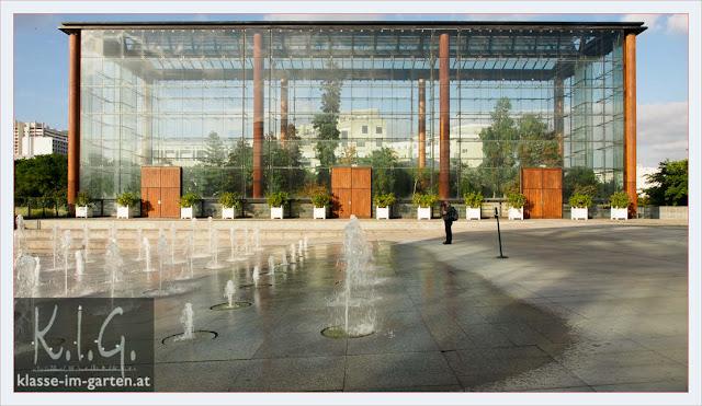 Eines der beiden Glashäuser im Parc Andre Citroen, im Vordergrund die auf und absteigenden Wasserfontänen-