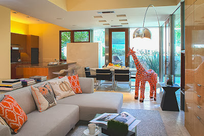 living room area with pops of orange and attractive girraffe figure