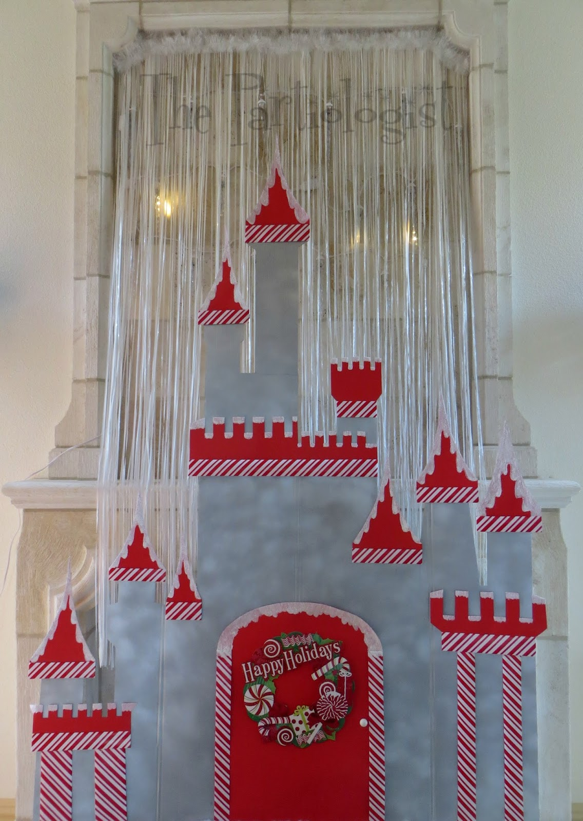 behind the castle i hung dripping icicle lights to resemble snow falling behind the castle i covered the cord with a white plastic door banner and topped