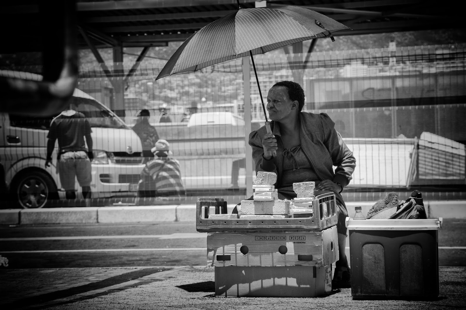 A vendor in the Cape Town taxi rank under her umbrella