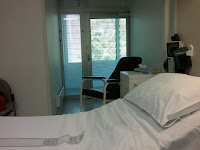 View of hospital room showing bed in the foreground, behind which is an alcove with an armchair and a glass door to a balcony outside.