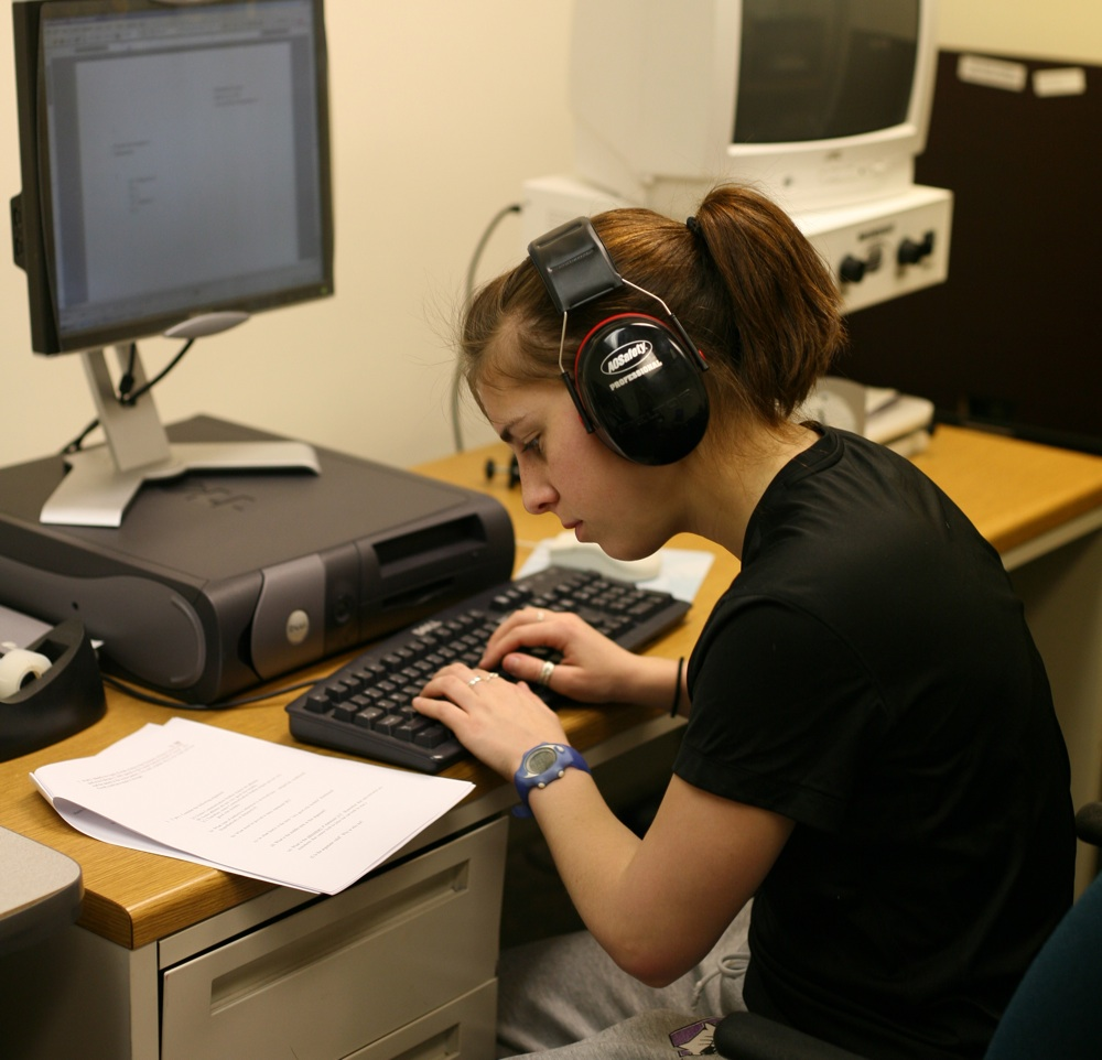 Woman wearing headphones sitting at a computer station