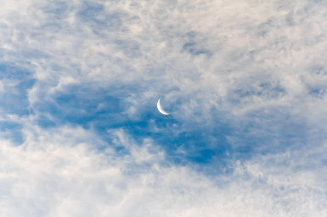 crescent moon behind evening clouds