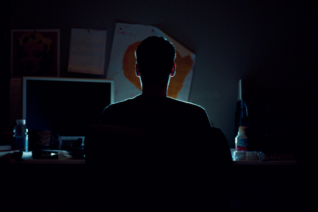 A man sitting late at night surfing the internet