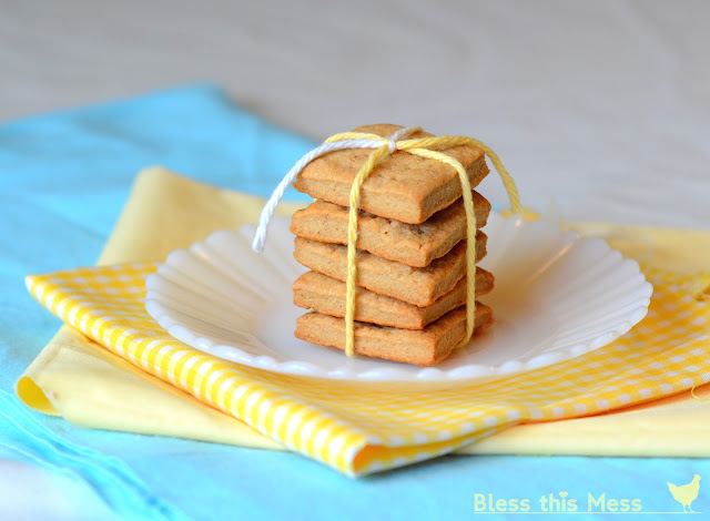 A stack of thick graham crackers tied together with string on top of a white plate.