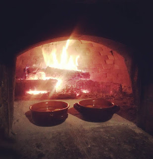 Two bowls in front of the fire in a traditional Tuscan oven