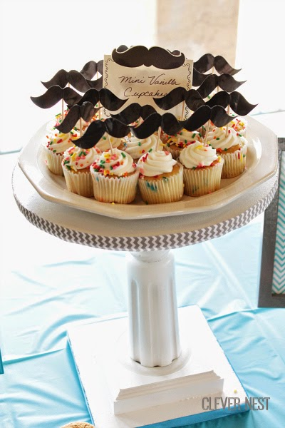 tablescape idea for mustache themed babyshower. Framed art doubles as nursery decor. Clever Nest #turquoisegraylime #littleman #hipsterbabyshower #glasses #bowtie #clevernest #bowtienapkins #babyshowergame