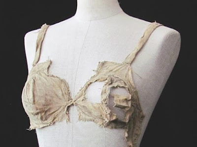 Photograph of a dummy form with a torn bra on it.