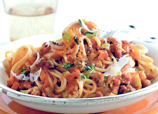 Basic bolognese sauce with beef served on a bed of spaghetti and garnished with parmesan shavings