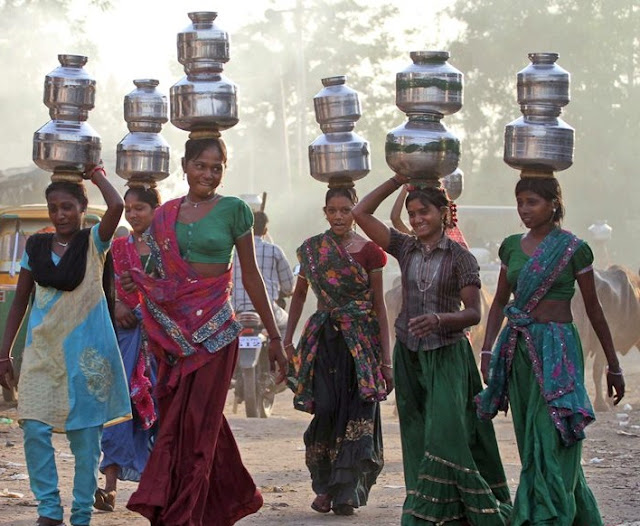 Women collect waterfrom a well.A rural life involves much contact with the elements.
