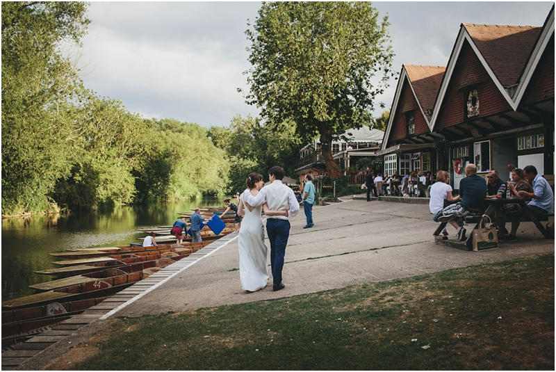 Bride and groom walking past punts at Cherwell Boathouse