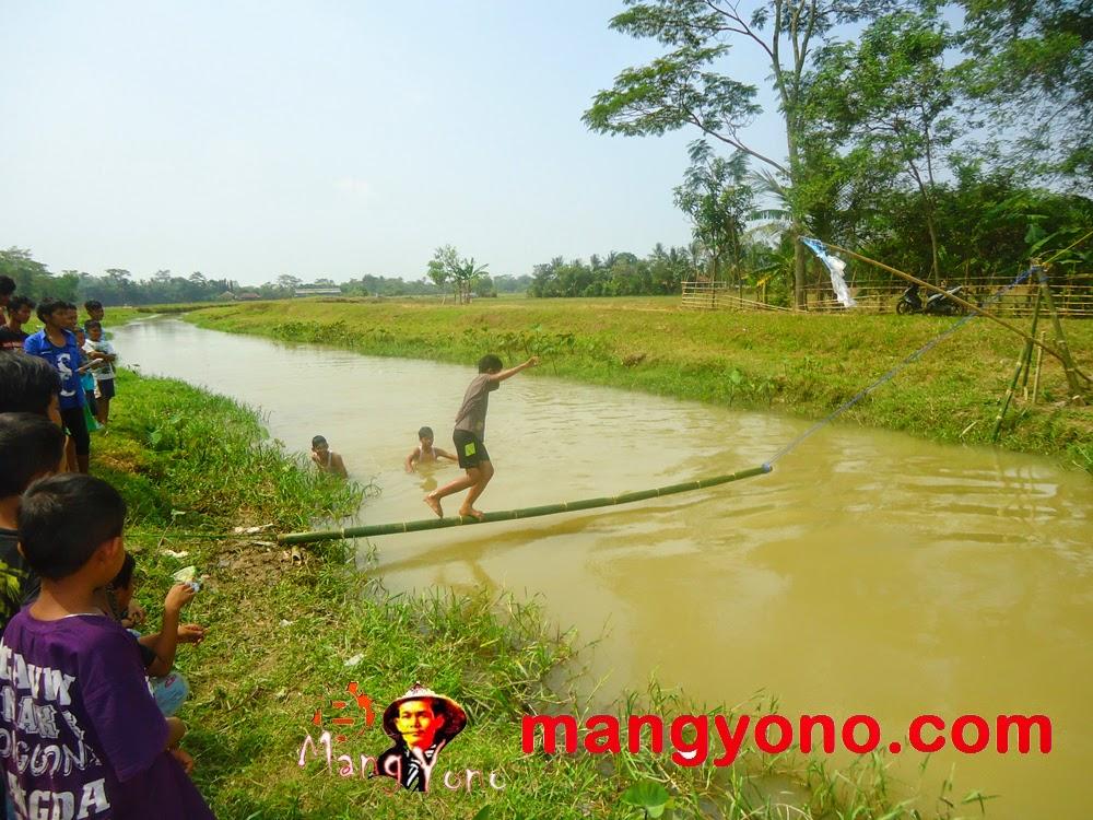 Seorang peserta diatas jembatan goyang dengan menjaga keseimbangan badan