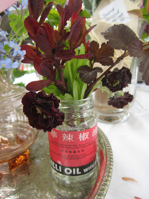 A dark double auricula and bright green meadowsweet arranged in an old chilli oil jar.