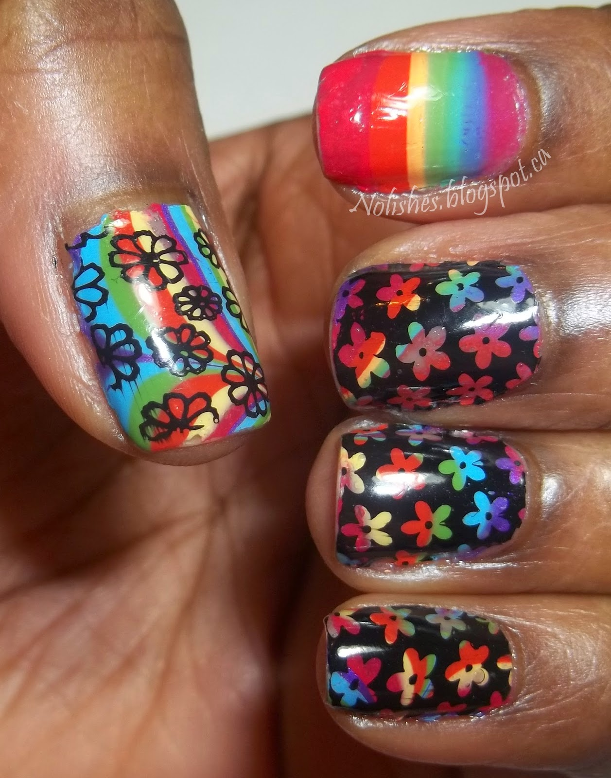 Nail stamping manicure featuring a rainbow coloured water marble base stamped with flower images in black. An index finger accent nail is left unstamped, and features bands of the colours of the rainbow.