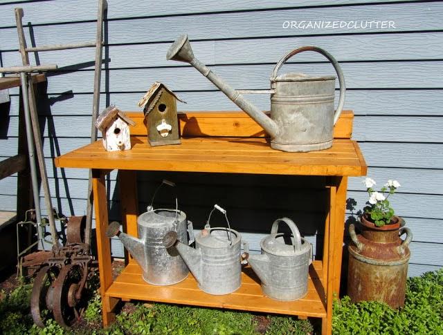 Junk Garden Waterning Cans www.organizedclutterqueen.blogspot.com