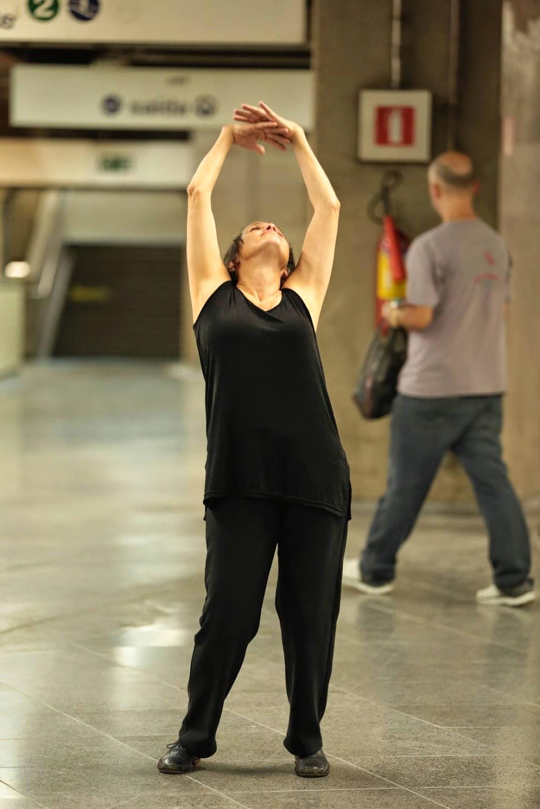 Descrição da Foto: Intérprete vestida de preto dança na plataforma do metrô. Está de pé com o rosto voltado para cima, braços para cima de mãos dadas. Pessoa passa no fundo.