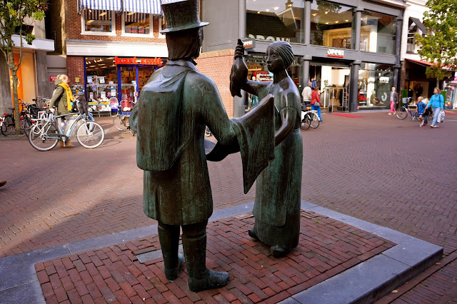 Statue of a peddler selling a piece of cloth to a peasant woman in Sneek, the Netherlands.