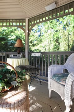 wicker chair on large wooden porch with railing