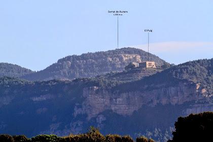 Zoom, des de l'alçada de Cal Conill Xic, al mas El Puig. Aquest es troba situat sobre els Cingles de Capolat i dins el terme homònim. Observem la coberta a quatre vessants i les galeries o porxos de la façana sud-est