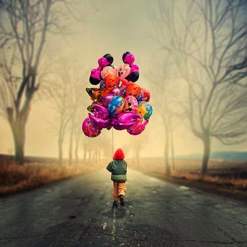 Niño por la calle con globos