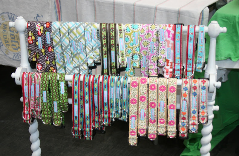 adorable dog collars in various sizes hung on a white rack