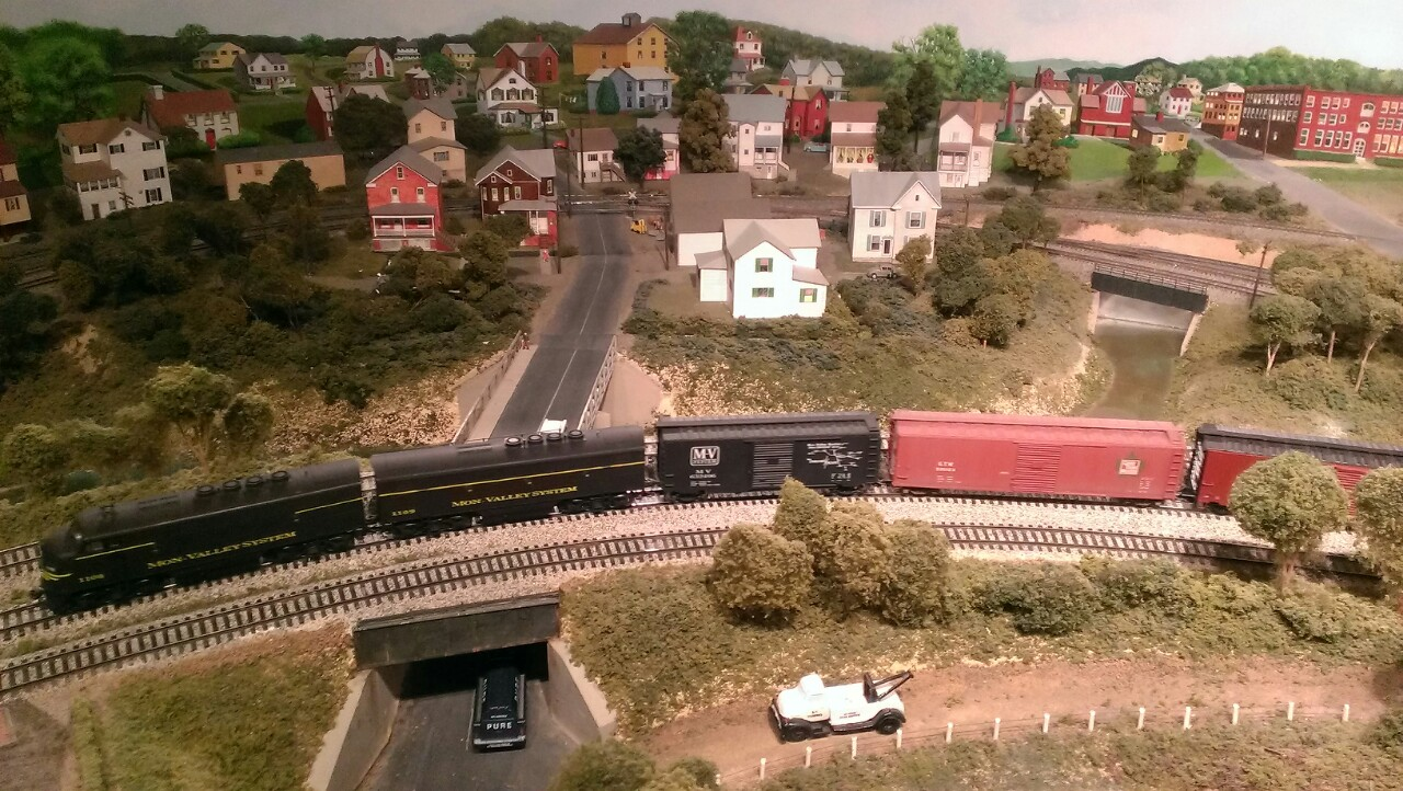 model train passing in front of houses