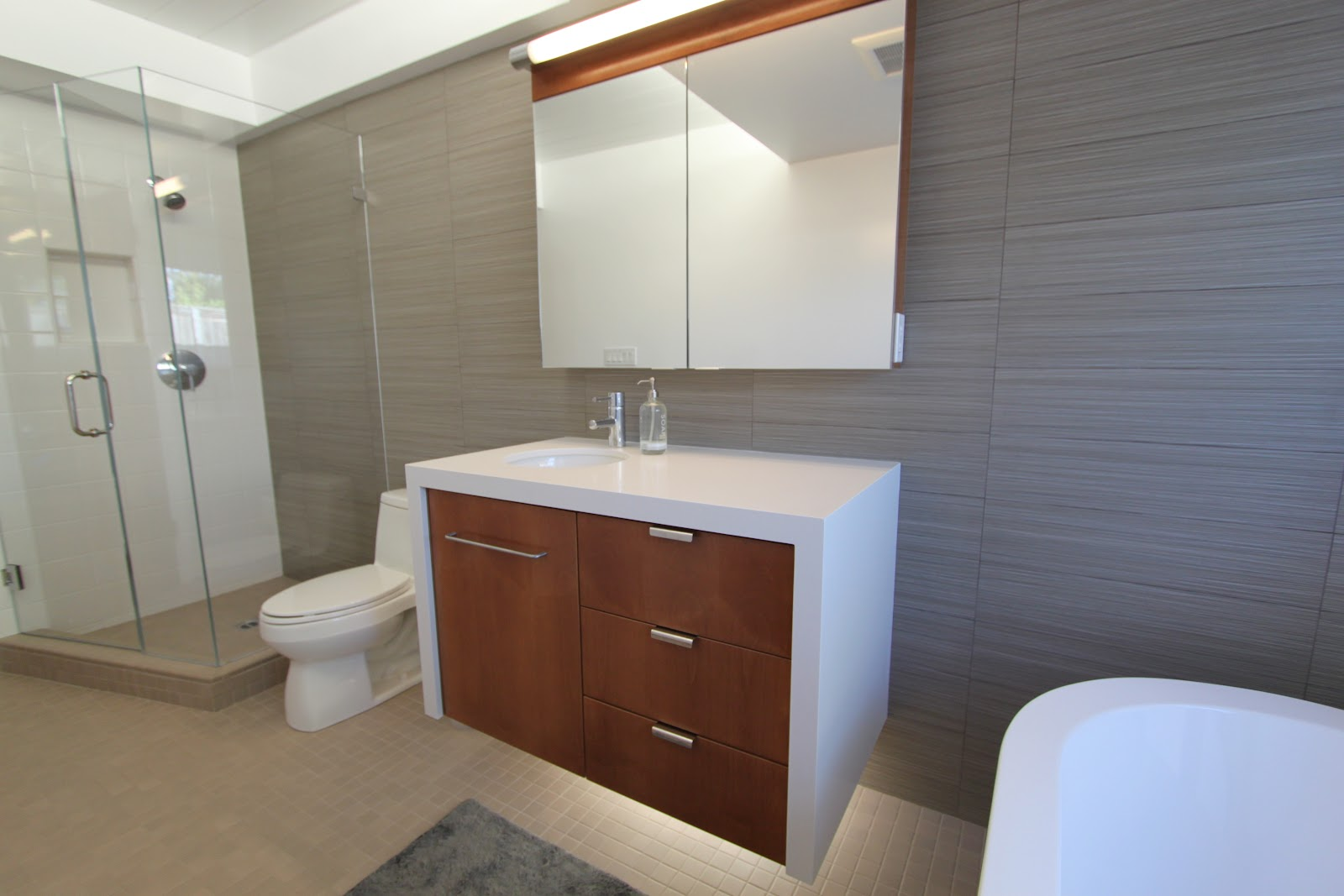 the new distinctly modern cabinets with a view of the clear glass shower - Bathroom Remodel Modern