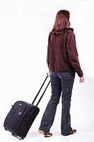 Photo of a woman wheeling a small suitcase