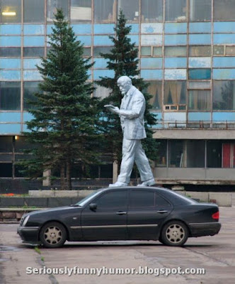 Big statue appears to be walking on top of a mercedes car.