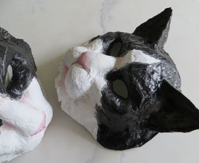 two paper mache cat masks by artist Shannon Reynolds
