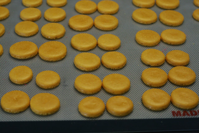 Pairs of baked macaron shells on a baking sheet that are matched according to size
