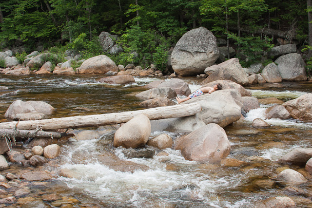 boy resting on a rock in the middle of a rocky river