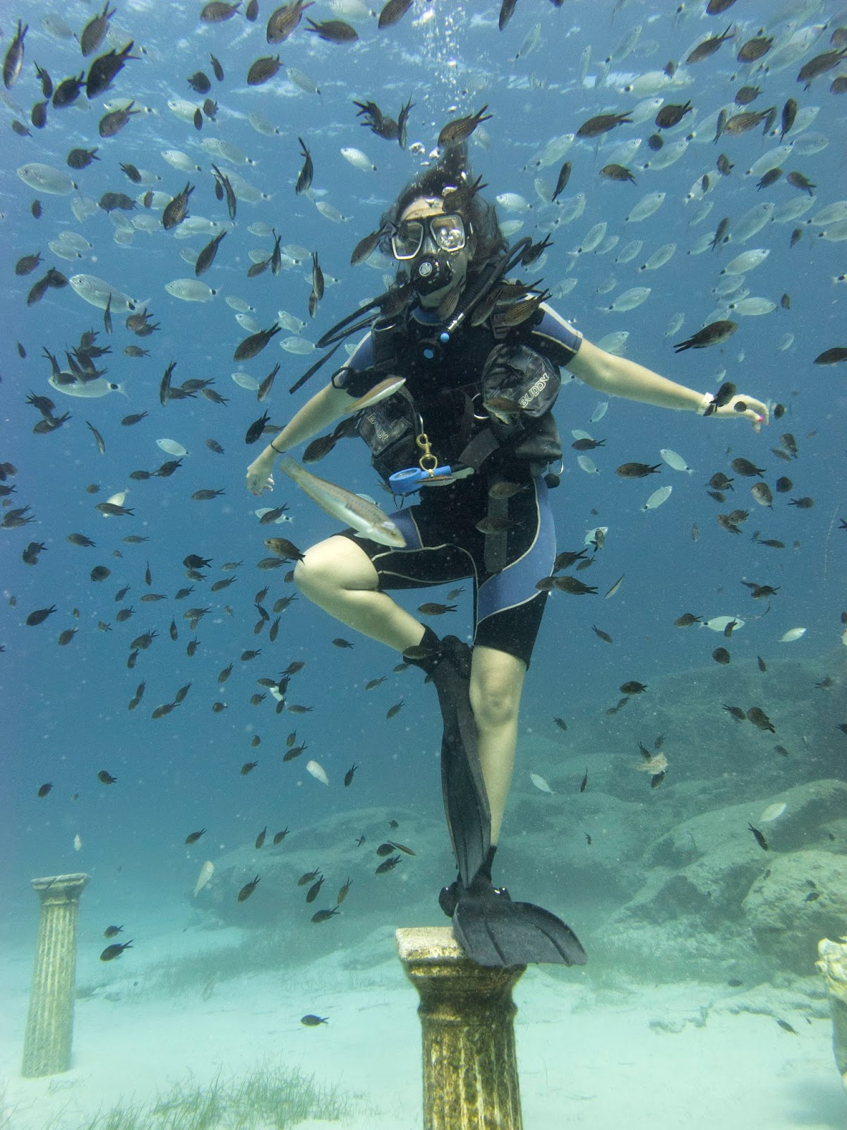 diver posing on underwater podium surrounded by fish