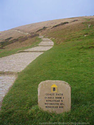 Coast path: Lulworth Cove, Durdle Door and the distance of other places far west. Camino costerto. Señal de piedra indicando la distancia en millas hasta llegar a Durdle Door, Ringstead, Weymouth. Dorset, England