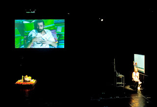 On the left of the stage, one actor is lying on a mattress, signing. A live cam projection shows his face and hands to the audience. On the right, an actress sits in a scenery representing a bathroom. She faces the audience and speaks into a microphone. The stage is dark except for spotlights on the actor and actress.