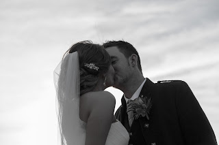 Bride and groom share a kiss. Bride has her hair loosely curled with soft volume. Pinned at the nape and accessorised with a sparkly hair comb and long flowing veil