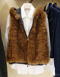 Brunello Cucinelli perfects the long white top look under a furry vest.