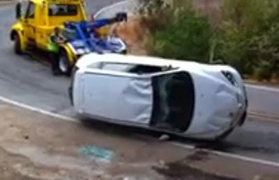 Operador de guincho atrapalhado faz carro virado cair em barranco