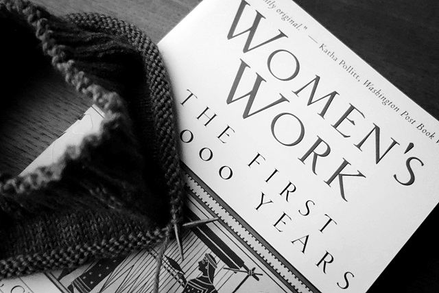 Knitting in progress, on a table with the book, Women's Work: the first 20,000 years.