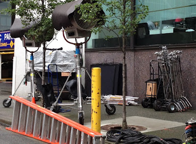 Lighting and gaffing equipment set up on the sidewalk at a film shoot