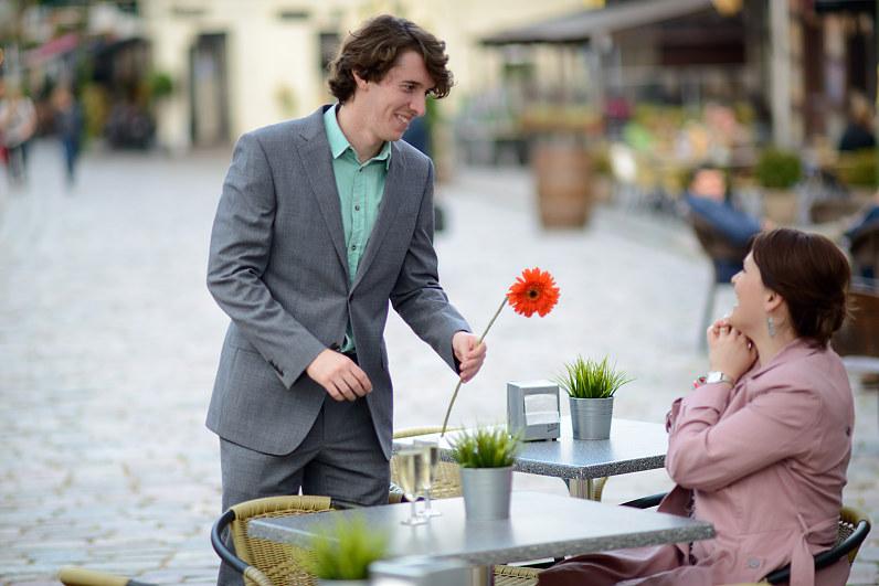 vyras pilku kositiumu su orandžine gėlė
