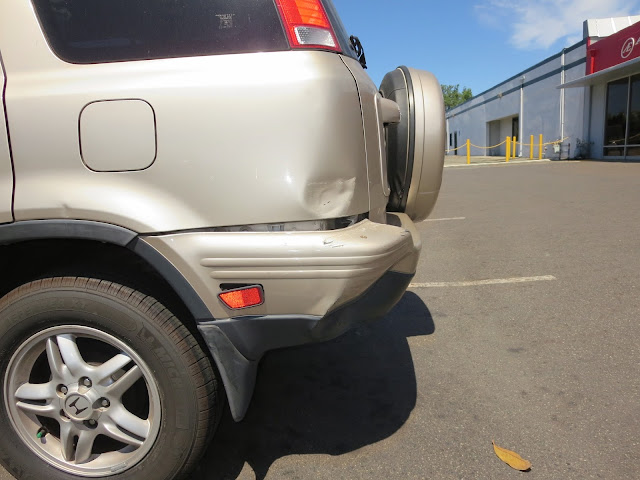 Dented quarter panel and bumper on Honda CR-V at Almost Everything Auto Body