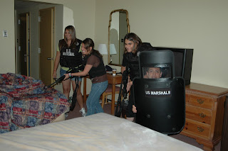 High school students from the 2010 Criminal Justice Summer Camp stage a mock raid on a hotel room using fake guns after a briefing by the U.S. Marshals Service.