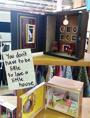 Dolls' house room boxes on a market stall next to a sign which says 'You don't have to be little to love a little house'