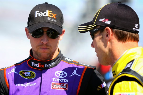 Denny Hamlin, driver of the #11 FedEx Express Toyota, talks to Matt Kenseth, driver of the #20 Dollar General Toyota, on the grid during qualifying for the 57th Annual Daytona 500 at Daytona International Speedway on February 15, 2015 in Daytona Beach, Florida. (February 14, 2015 - Source: Maddie Meyer/Getty Images North America)