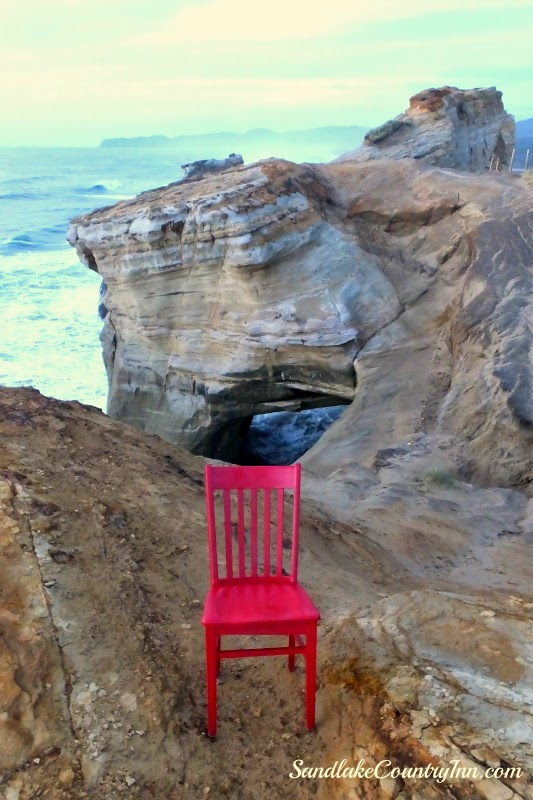 red chair sitting on Cape Kiwanda
